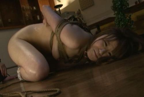 縄で縛られ床に伏せている女性